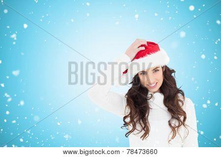 Confused brunette in santa hat against blue vignette