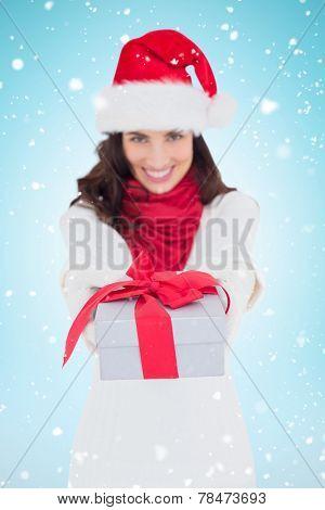 Festive brunette in santa hat giving gift against blue background with vignette