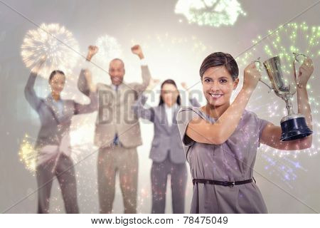 Woman holding up a cup with enthusiastic coworkers against colourful fireworks exploding on black background