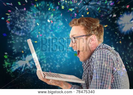 Geeky businessman using his laptop against colourful fireworks exploding on black background