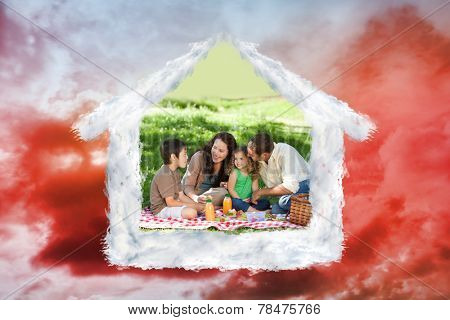 Family picnicking together against green grass under red cloudy sky