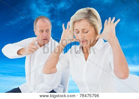 Older couple sitting in chairs arguing against blue sky