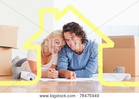 Couple organizing their future home against house outline
