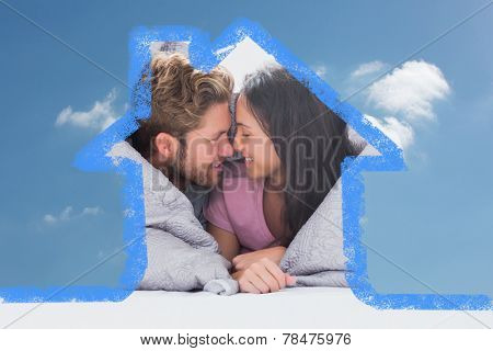 Couple wrapped in the duvet against cloudy sky
