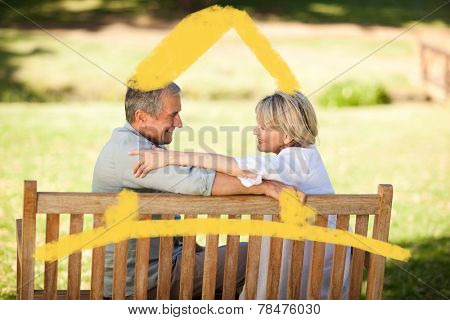 Happy retired couple sitting on the bench against house outline