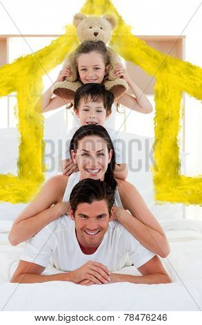 Young Family playing on bed together against house outline in clouds