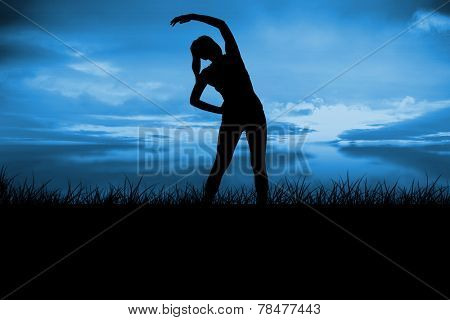 Fit brunette stretching and smiling against blue sky over grass