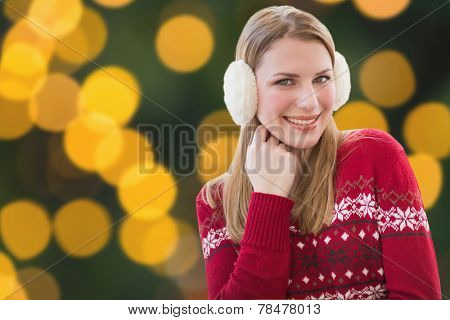 Woman wearing warm ear muffs against blurry yellow christmas light circles