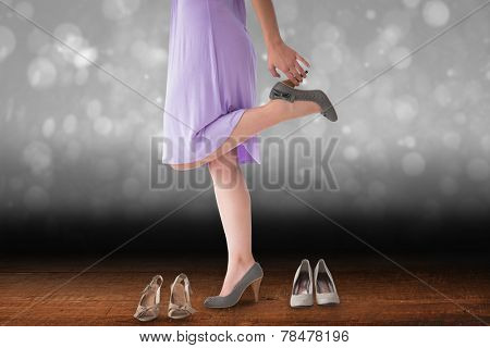 Mid section of woman trying heels against shimmering light design over boards