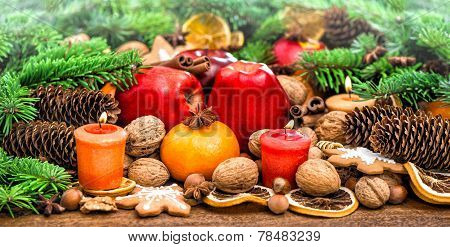 Fruits, Cookies Nuts And Candles With Christmas Tree Branches