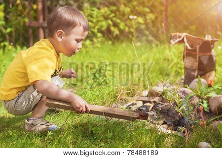 Caucasian Little Boy Dealing With Fire Near Firepace Outdoors.