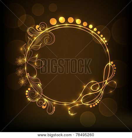 Shiny golden frame decorated by beautiful floral design on brown background.