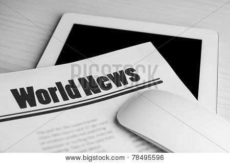 On-line news concept. Computer mouse, PC tablet and newspaper, close-up