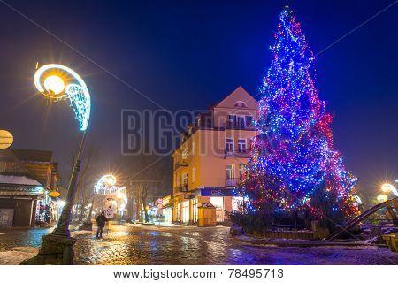 ZAKOPANE, POLAND - DECEMBER 6, 2014: Christmas tree on the Krupowki street in Zakopane. Krupowki street is the main shopping area and pedestrian promenade in the center of Zakopane, Poland.