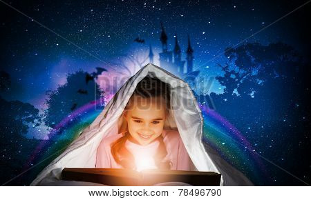 Little cute girl with in bed reading book under blanket
