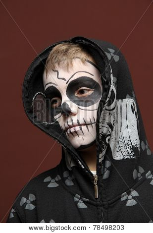 Boy with halloween zombie make up on brown