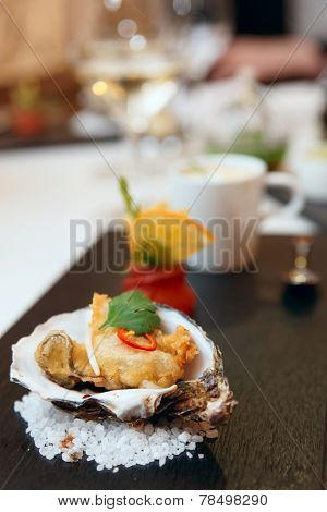 Tempura fried oyster in shell on restaurant table