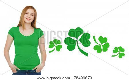 gestures, holidays, st. patricks day and people concept - happy teenager in blank green t-shirt over white background with shamrock or clover