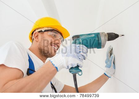 building, working equipment and people concept - smiling builder in hardhat perforating wall with electric drill indoors