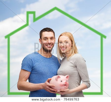 love, home, people and family concept - smiling couple holding piggy bank over green house and blue sky with grass background