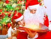 stock photo of granddaughter  - Santa Claus with little granddaughter opening magic book and saw glowing lights - JPG