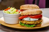 foto of chickpea  - Vegetarian chickpea burger tomato and dip of herbs garlic and yogurt and salad with cherry tomatoes - JPG