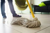 stock photo of housekeeper  - Woman at home doing chores and housekeeping wiping floor with water in living room - JPG