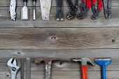 picture of pry  - Top view of basic used partial tools forming border on rustic wooden boards - JPG