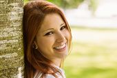 stock photo of redhead  - Portrait of a pretty redhead smiling against trunk in park - JPG