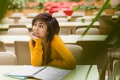 pic of canteen  - Young female college student doing homework in outdoor canteen - JPG