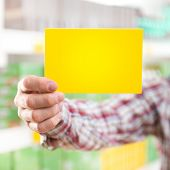 stock photo of dungarees  - Farmer in checked shirt and dungarees holding a sign at supermarket - JPG