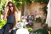 stock photo of scooter  - Young beautiful italian woman sitting on a italian scooter - JPG