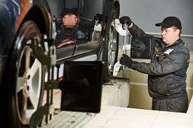 image of suspension  - car mechanic installing sensor during suspension adjustment and automobile wheel alignment work at repair service station - JPG