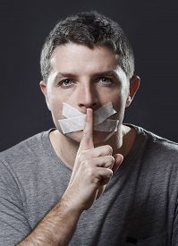 pic of freedom speech  - attractive young man with mouth sealed on duct tape to prevent him from speaking keeping him mute and censored in freedom of speech and expression concept - JPG