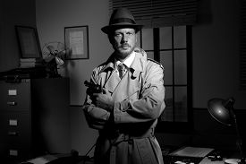 stock photo of revolver  - Attractive detective holding a revolver with retro office on background film noir - JPG