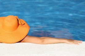 picture of bathing  - Woman with an orange picture hat bathing relaxed in a pool water enjoying vacations with blue background - JPG