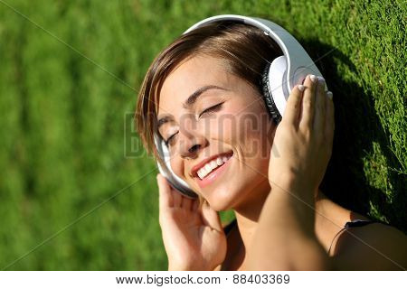 Happy Girl Listening To The Music With Headphones In A Park