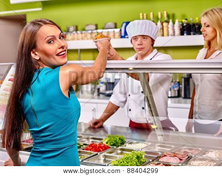 Women at cafeteria buying food. Seller sells girl cupcake