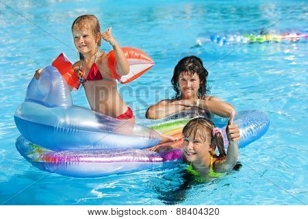 Family with children in swimming pool. Summer outdoor. Floating  mattress.