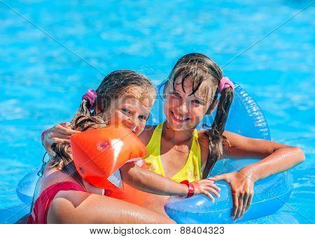 Little girl swimming on inflatable beach mattress. Loving sister.