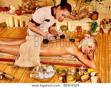 Woman getting stone therapy massage in bamboo spa. Two people.