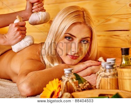 Blond woman getting herbal ball massage in spa. Look at camera.