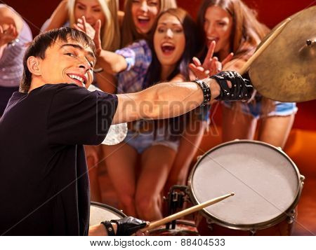 Man knocking on drum in night club.