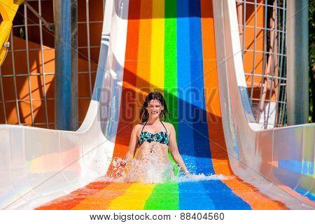 Happy woman in bikini sliding water park. Rainbow color.