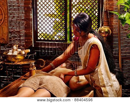 Young woman having oil Ayurveda spa treatment. On window background.