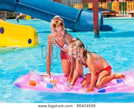 Child on water slide at aquapark. Inflatable beach mattress.
