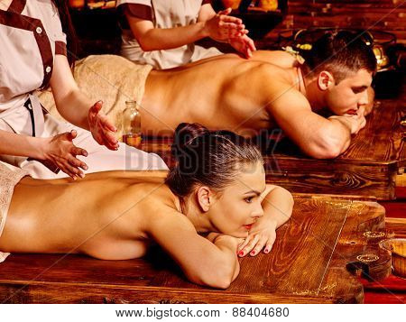 Couple  having oil Ayurveda spa treatment. Wooden bed.