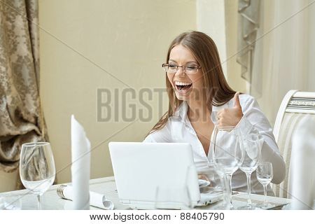 Laughing businesswoman showing thumbs up at lunch