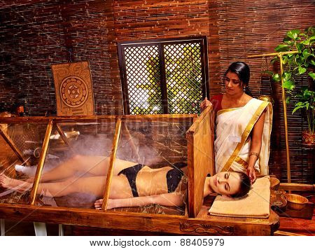 Woman having Ayurvedic sauna treatment. Wooden structure.