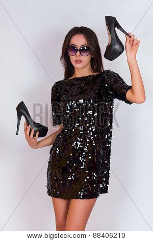 Beautiful brunette girl in a black dress and glasses, holding black high-heeled shoes.